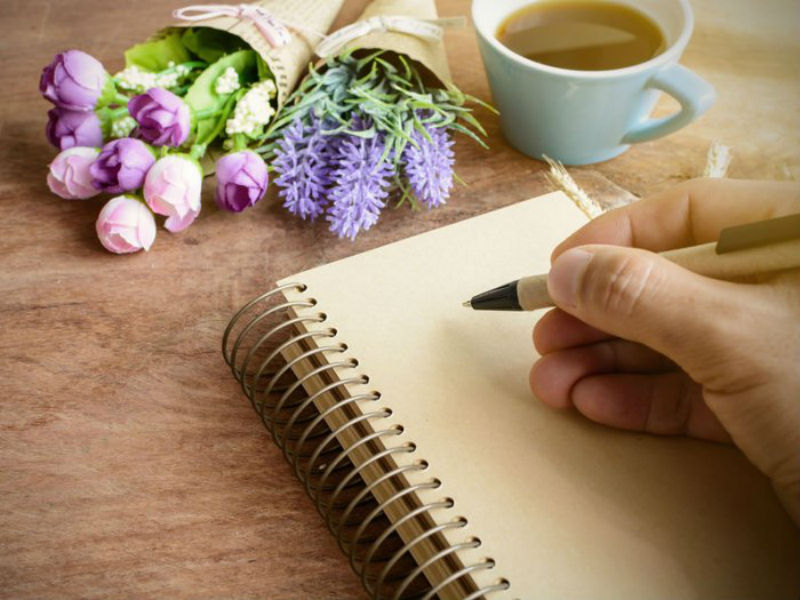 Jotting funeral wishes in a notebook