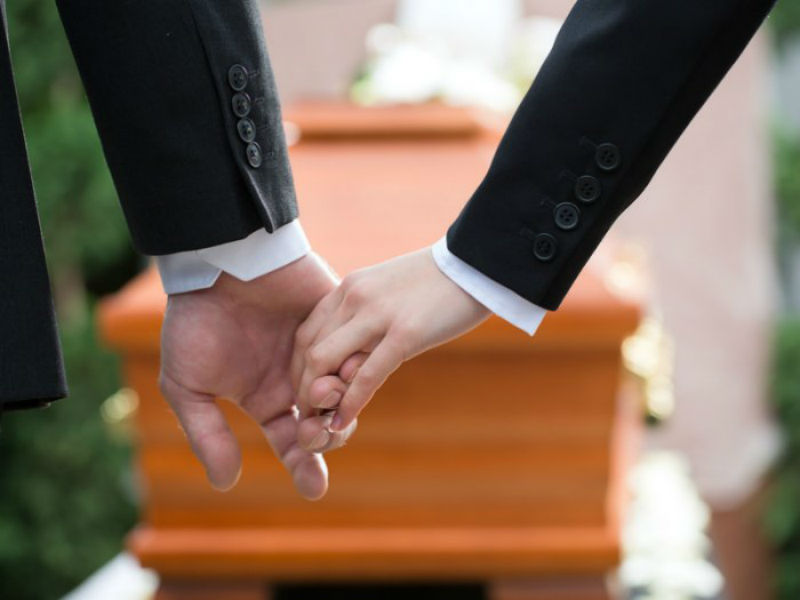 A bereaved couple hold hands at a funeral