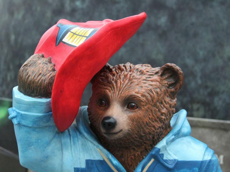 A statue of Paddington raising his hat