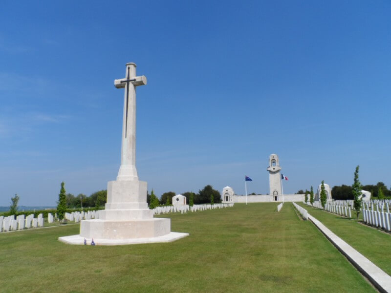 View of the Villers–Bretonneux memorial, with the cross of sacrifice in the foreground, and gravestones and the Australian and French flags visible