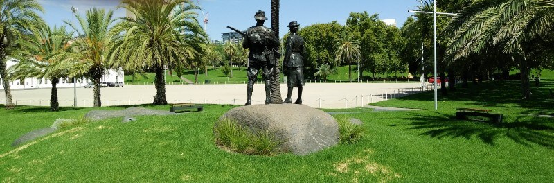 Rear view of Aboriginal and Torres Strait Islanders War Memorial; lifelike sculptures of male and femal soldiers in battledress standing on a large rock in a park