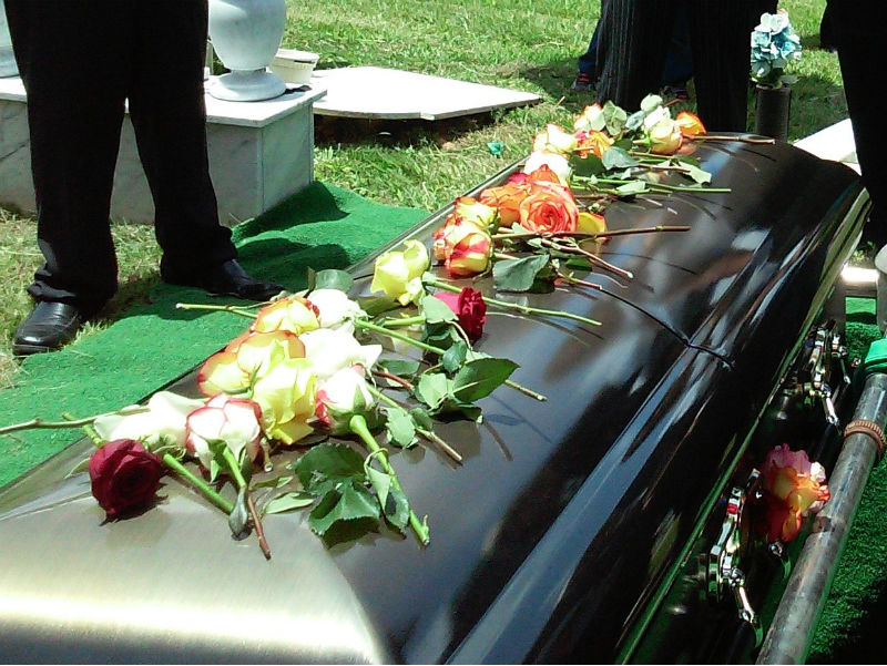 casket with flowers an d people standing around