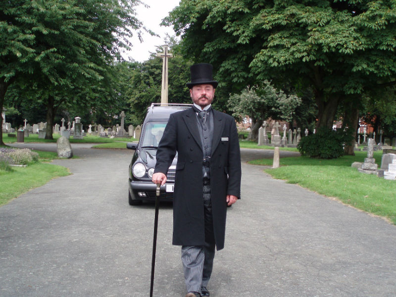 funeral director leading a hearse