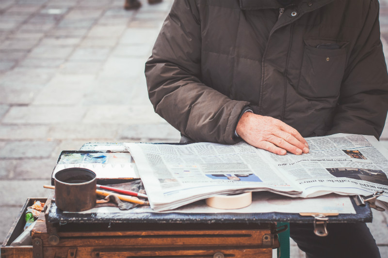 A man reading a newspaper in the street