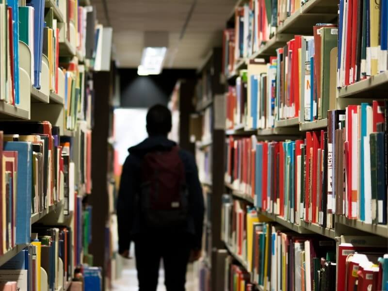 Student walking between library shelves in semi-darkness
