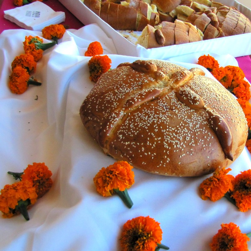 Photo of bread of the dead on a white table cloth scattered with marigolds