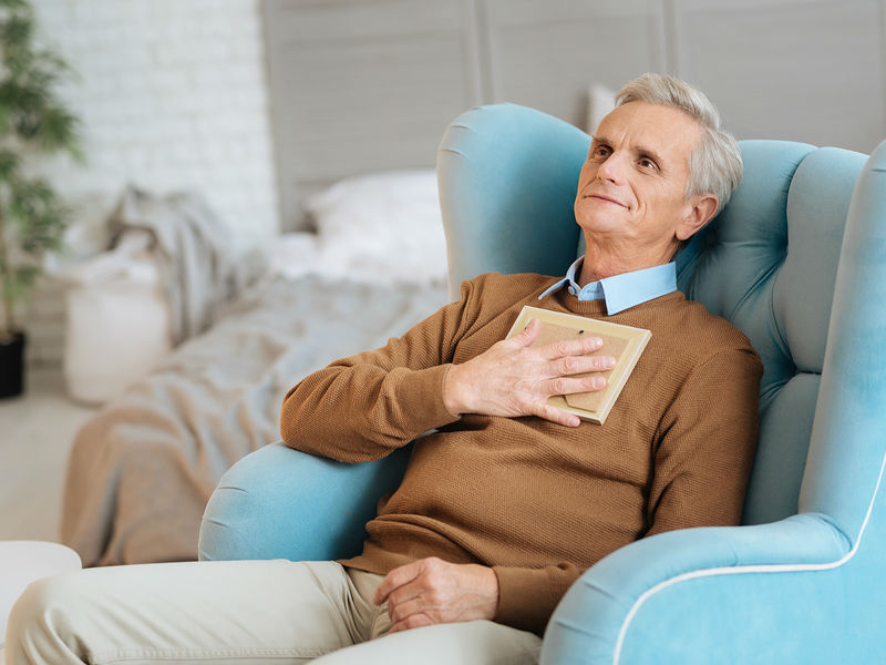 Old man feeling loved with picture frame via Bigstock