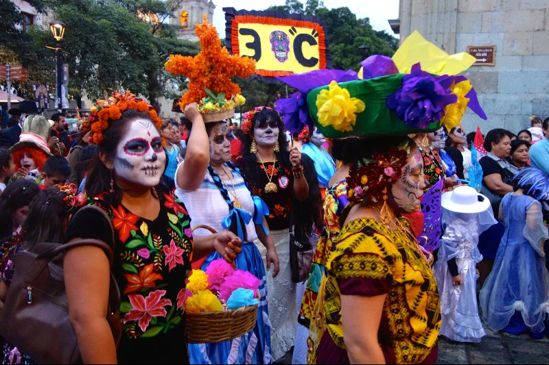 Photo of people with painted faces and traditional costumes at a Day of the Dead parade in Mexico