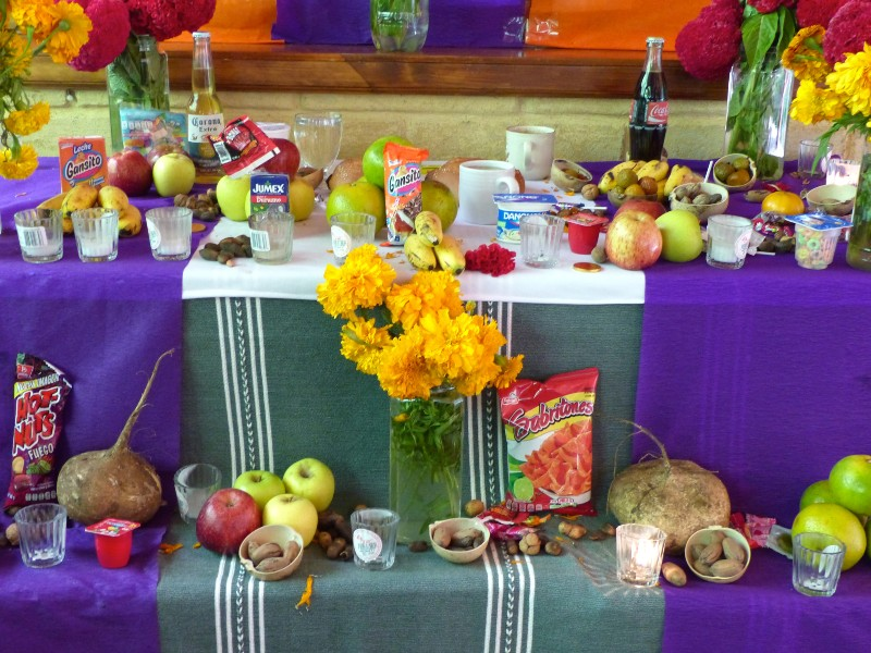 Photo of a Day of the Dead Shrine decorated with skeleton toys, candles, fruit, bread and flowers