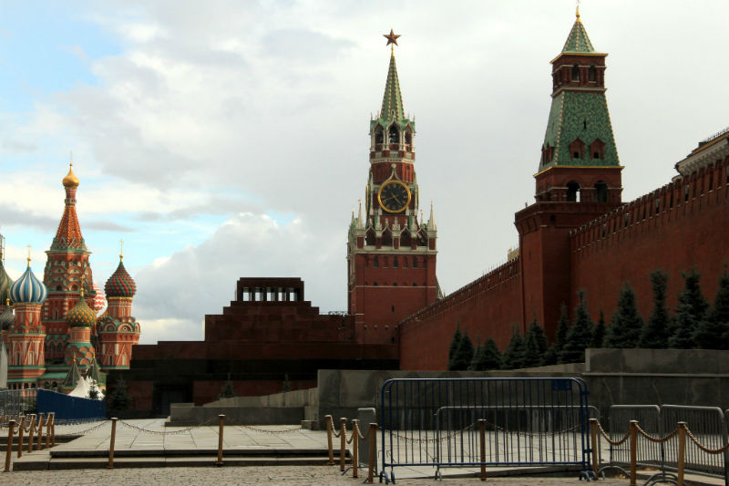 Wide shot of Lenin mausoleum in red square with St. Basil's cathedral in the background