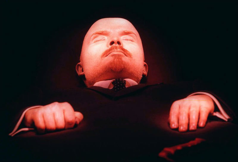 Close-up of the head and shoulders of Lenin's mummified body under red light