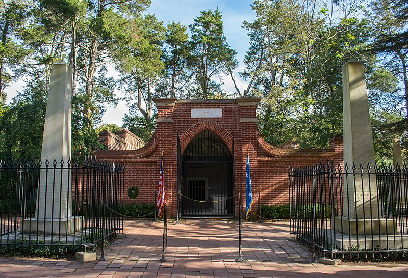 Exterior view of the Washington Family mausoleum new tomb on the Mount Vernon Estate, with an American flag on a stand in front of it