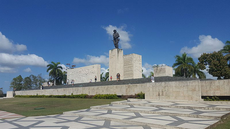 Wide shot of the Che Guevara mausoleum with people viewing his statue from the front steps