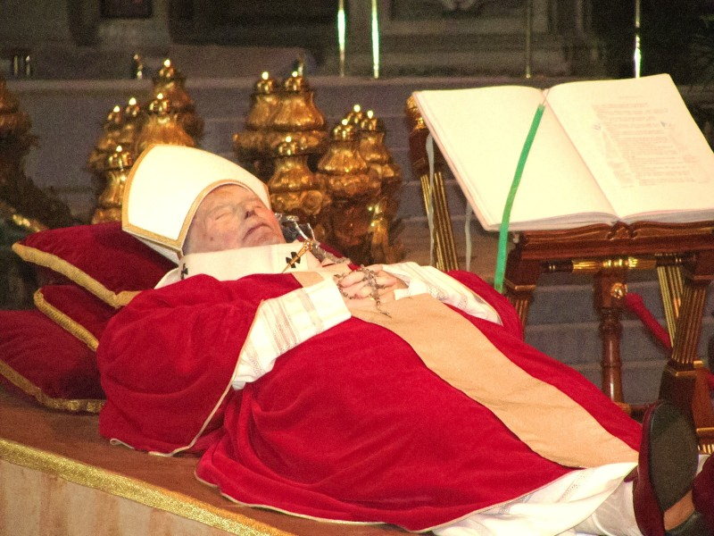 Body of Pope John Paul II in red ceremonial papal clothes on catalfalque