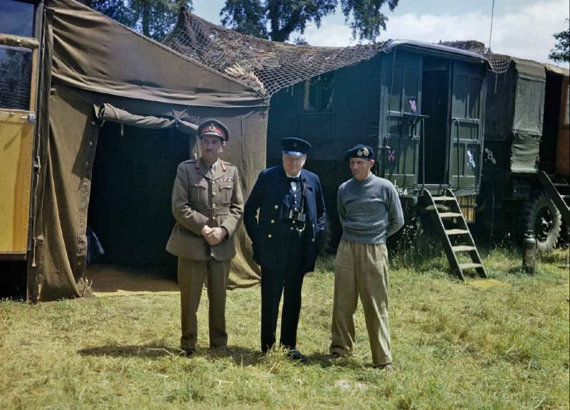 Colour photo of Winston Churchill in blue suit and RAF forage cap with Field Marshal Montgomery and General Brooks standing in front of a tent on an army base during WW2