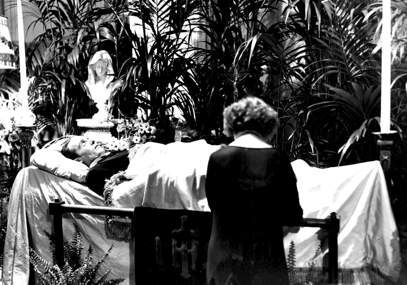 Black and white photo of Rudolph Valentino in open coffin surrounded by plants with woman mourning over his body