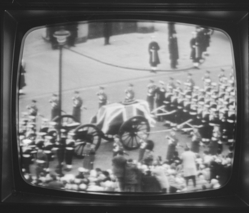 Black and white photo of Winston Churchill's funeral procession, including his coffin draped in a Union Jack on a gun carriage, being viewed on a television screen