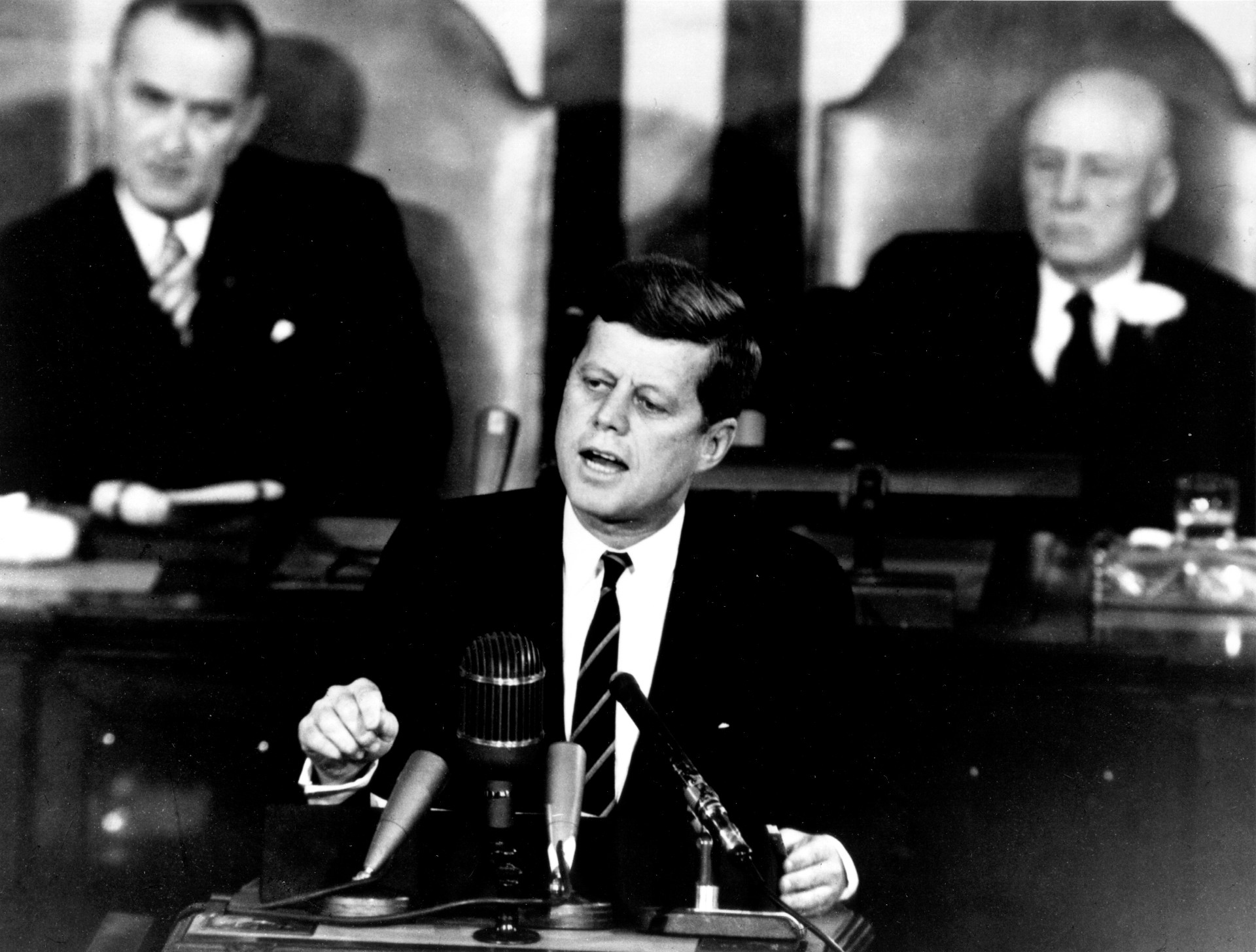 Black and white photo of President John F. Kennedy delivering speech announcing the USA's intention to land on the moon by the end of the 1960s