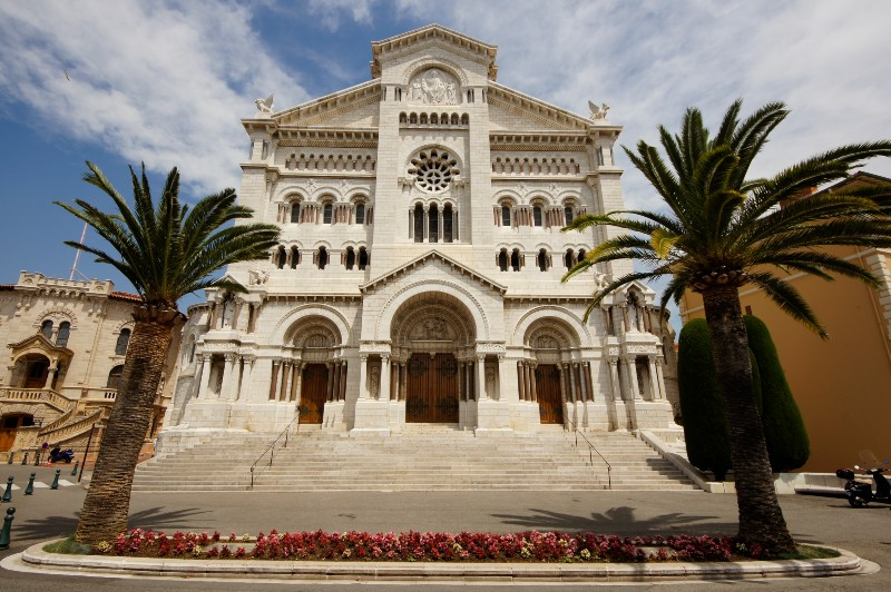 Colour photo of the front of Monach cathedral, with flowerbed and palm trees at the front