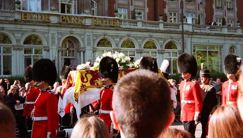 Close-up of Princess Diana's coffin draped with the Royal Standard escorted by Guardsmen, with mourning members of the publi in shot