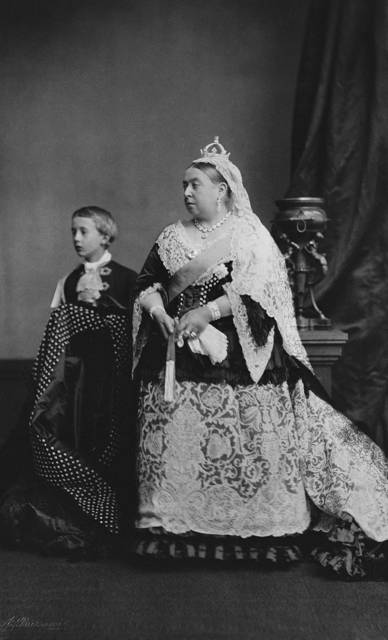 Black and white photo of Queen Victoria in royal regalia, with crown and sash, with a page boy in the background