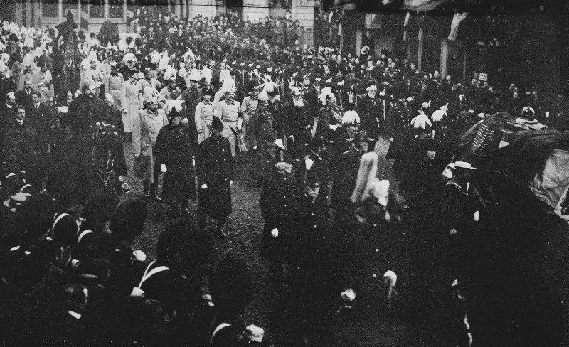 Black and white photo of Queen Victoria's funeral procession, with coffin topped with crown and sceptre in view, escorted by guards and watched by public mourners