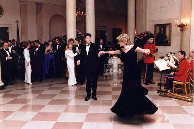 Photo of Princess Diana in a black dress dancing with John Travolta, in a tuxedo, at the White House
