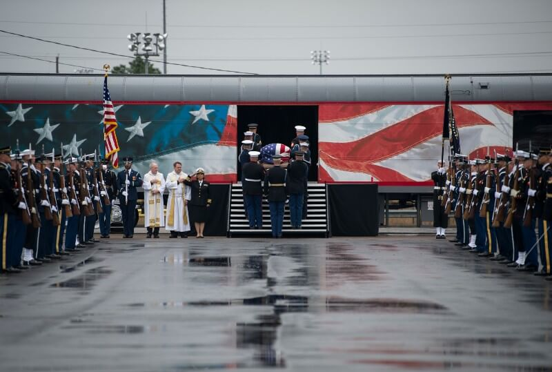 Colour photograph of George H.W. Bush's funeral train being carried on to his funeral train by a US Navy honour guard