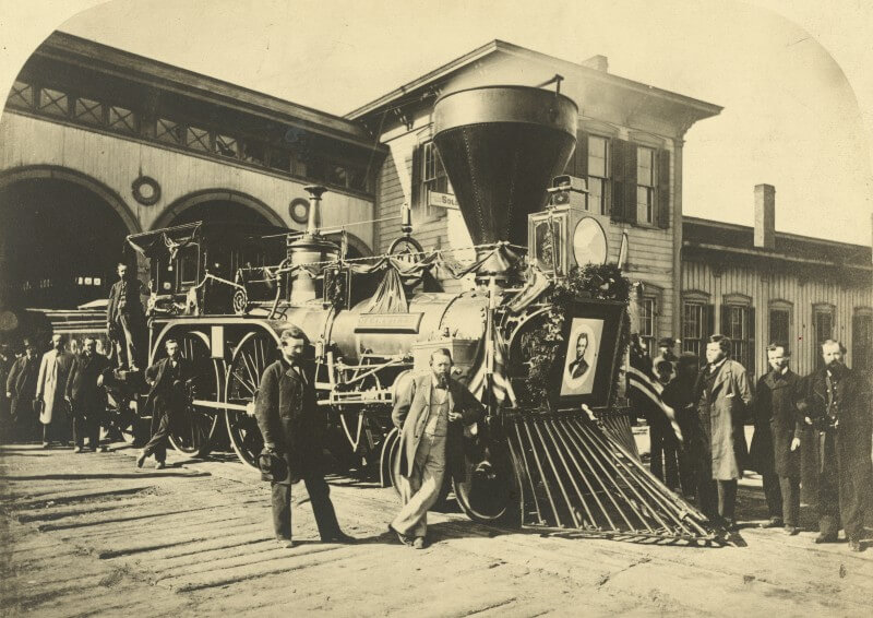 Photo of Abraham Lincoln's funeral train with picture of the president surrounded by a wreath on the front and surrounded by men posing for the picture