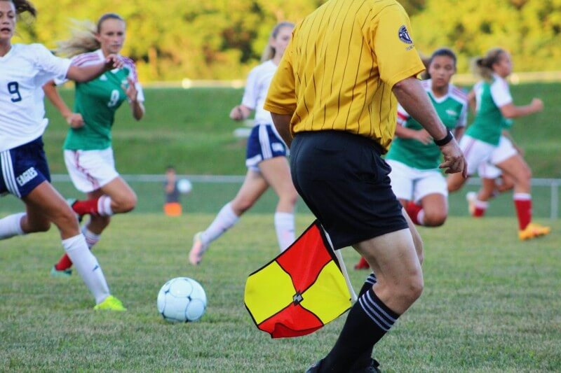 Woman playing football in kits with an assistant referee in the foreground