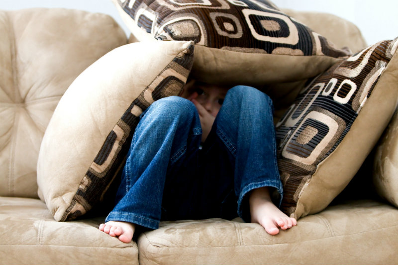 A child hiding under some pillows on a couch