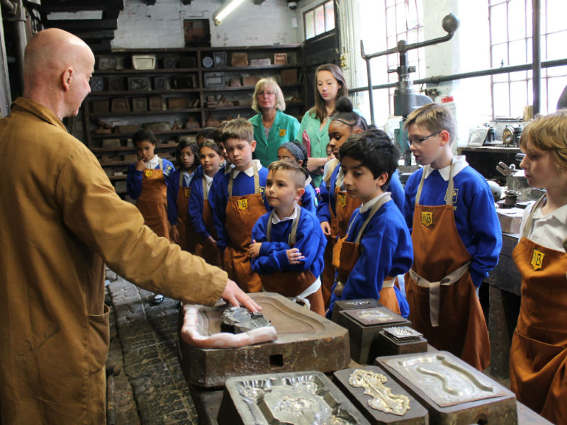 A group of children learn how things were made at living heritage museum Newman's Coffin Works