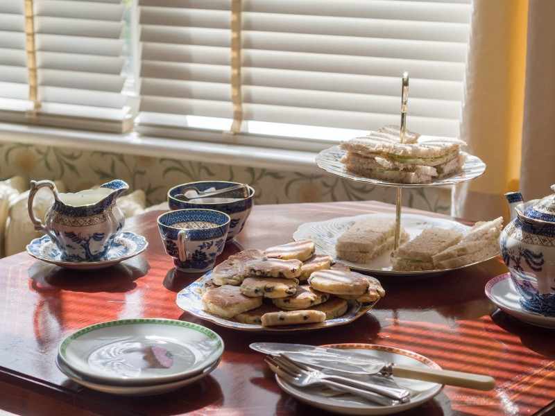 Photo of tea set on a table by a window, with platters of cucumber sandwiches and Welsh cakes