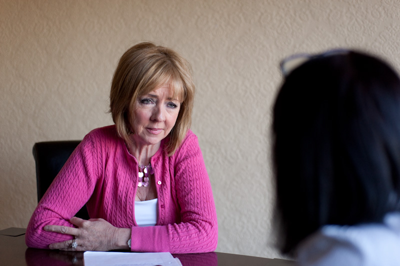 Picture of lady in pink cardigan sitting at a table and speaking to another women about their choices for a funeral