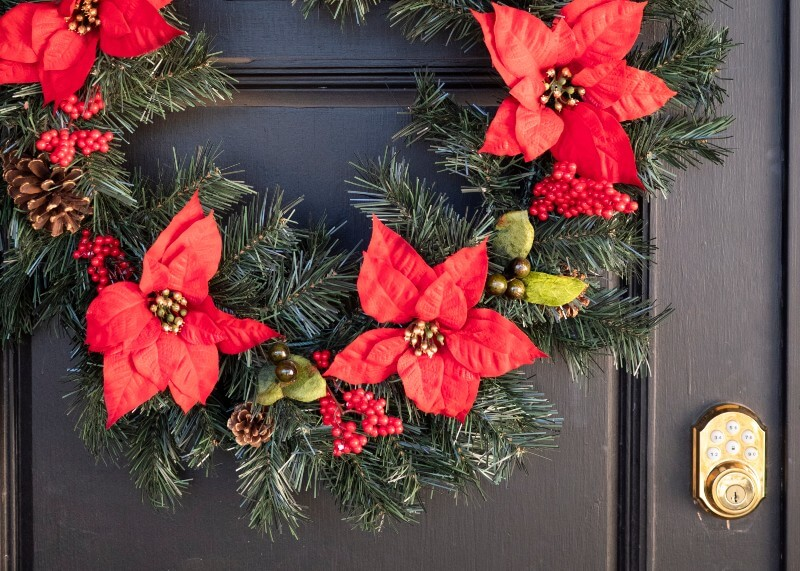 Christmas wreath hanging on a dark brown wooden door