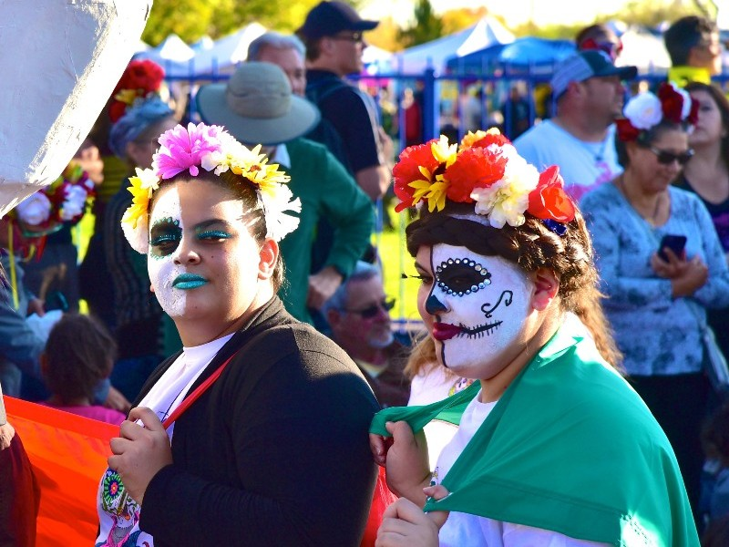 Photo of two women in skull facepaint and floral head-dresses at a Day of the Dead festival in Albuquerque, New Mexico