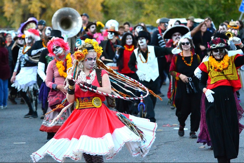 Photo of Day of the Dead parade in America, with people in traditional costumes, face paint and marigold decorations