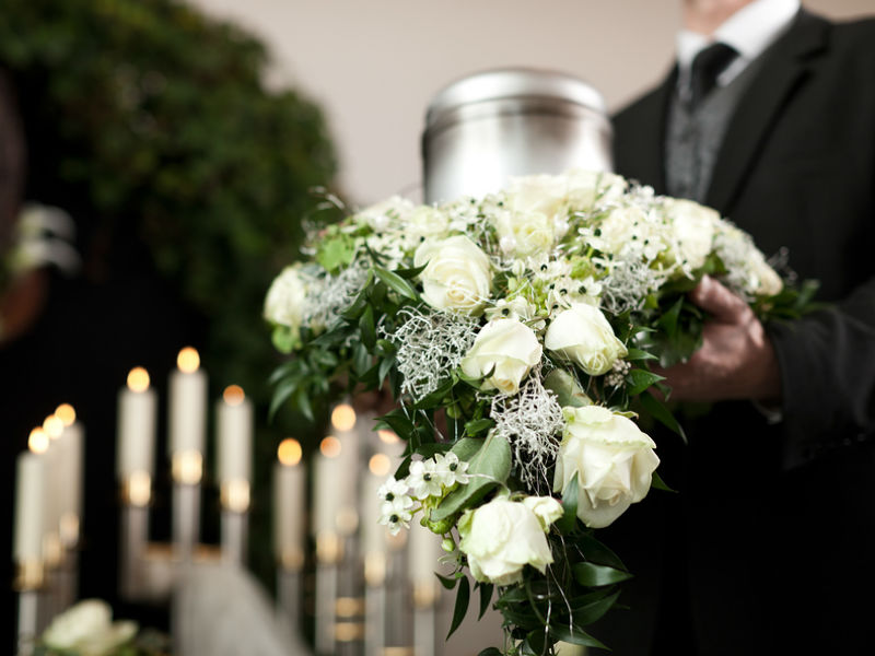 a funeral director holding a wreath