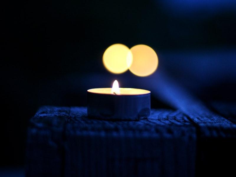 A lit votive candle on a blue background!