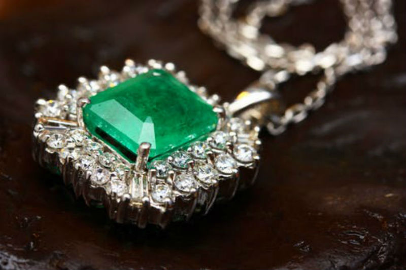 Close-up of a silver necklace with a large emerald stone and diamonds embedded in the surround