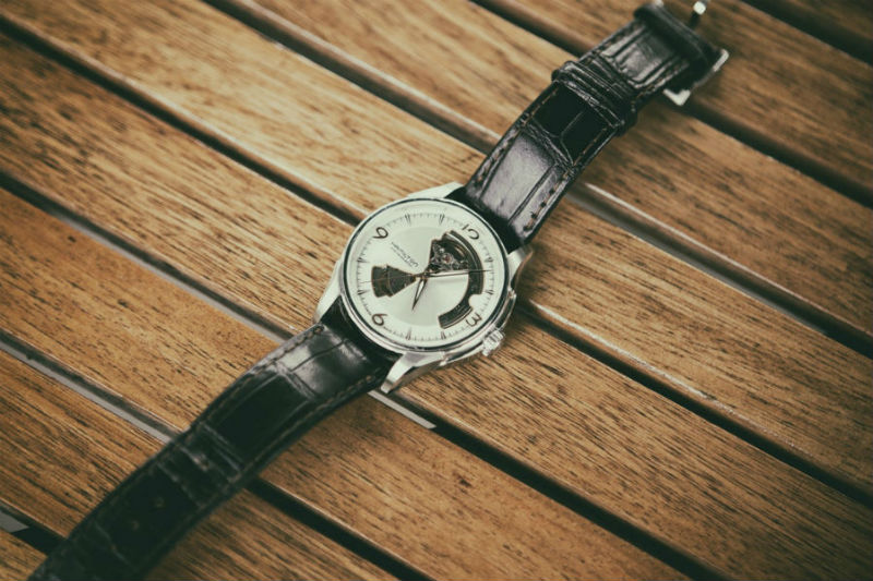 Analogue watch with a silver roundel and black leather strap lying on a wooden slats