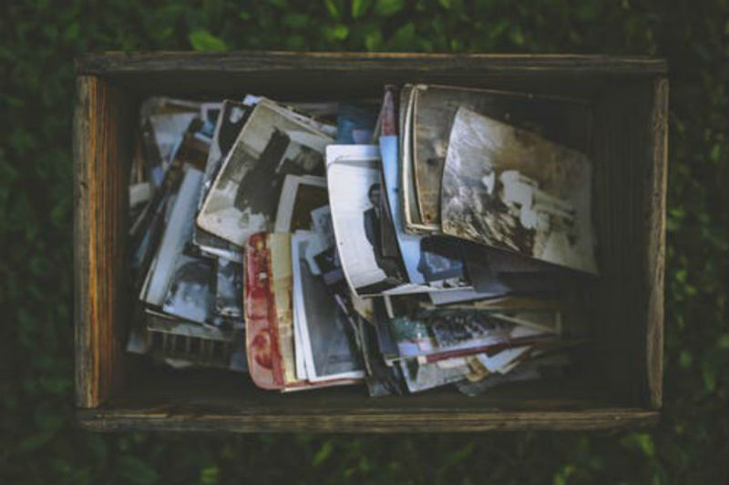Arial view of photographs in a large wooden box on a bed of green leaves