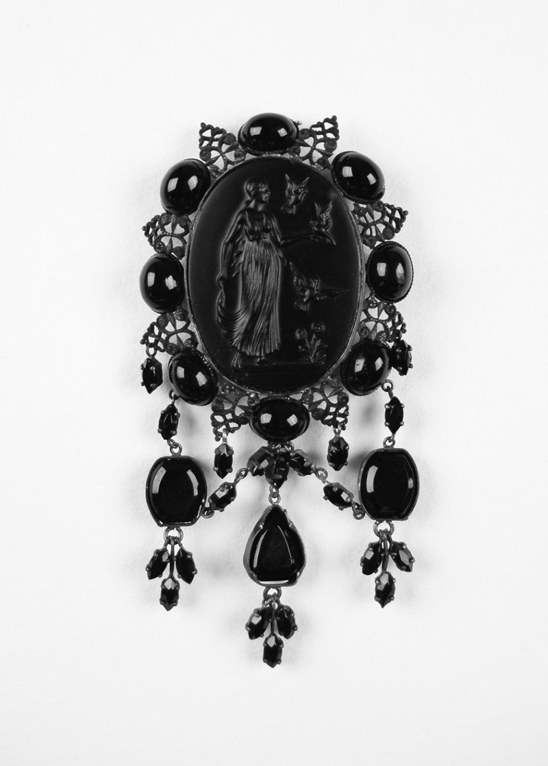 Jet charm with engraving of young woman surrounded by birds in flight in the centre and smaller beads with filligree work and smaller beads on the edge