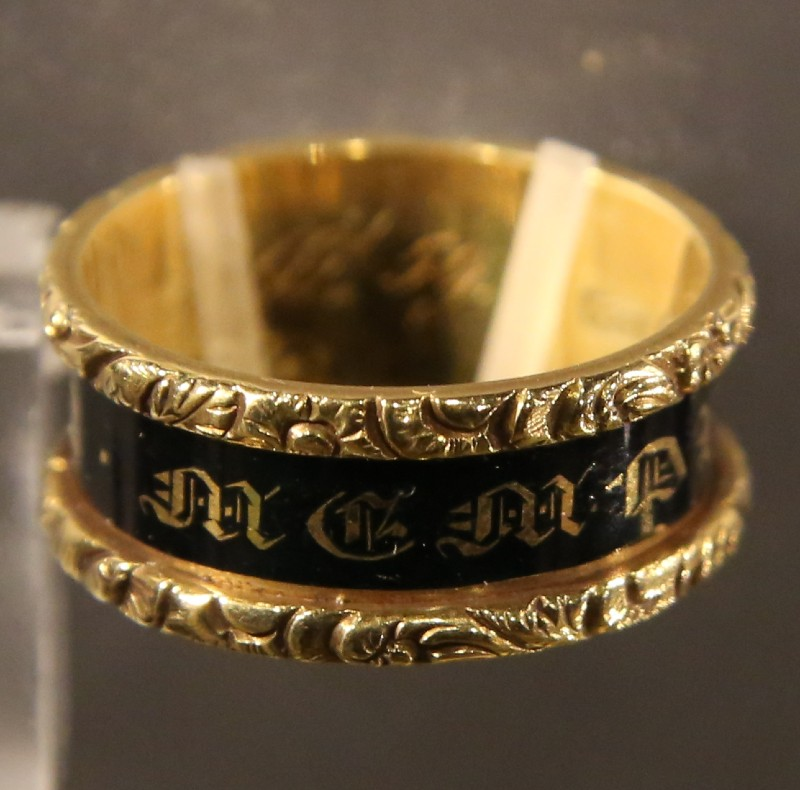 Close-up of gold mourning ring, with black enamel band inscribed witH indistinct gold lettering