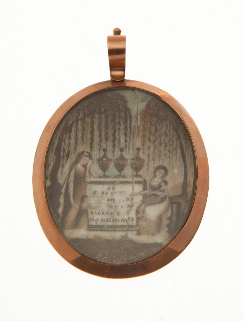 Close-up of locket with image of two women mourning at a stone memorial with 3 urns on top, depicting in hair