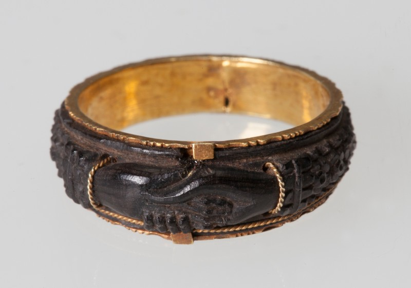 Close-up of mourning ring with gold inner band and wooden deocration, with carving of clasped hands
