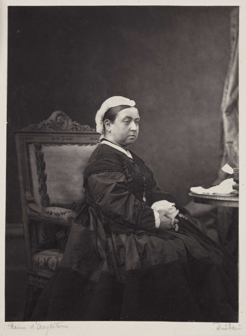 Photo of Queen Victoria in black mourning dress and white headdress sitting on a chair at a table