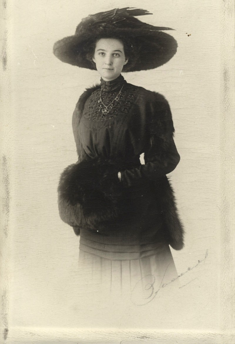 Victorian photograph of young woman in mourning clothes; wearing a balck dress, large feathered hat and jewellery