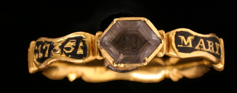 Close-up of post-medieval gold mourning ring, with pale purple gemstone and black enamel panels inscribed with the words '1735' and 'Mary