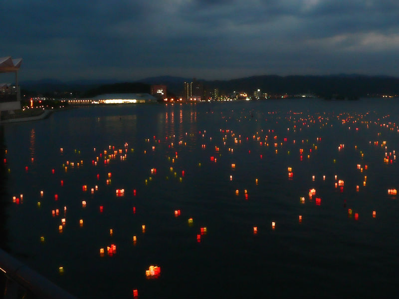 Hundreds of small paper lanterns floating on a lake at night